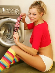 Sexy blond girl strips and poses while doing her laundry